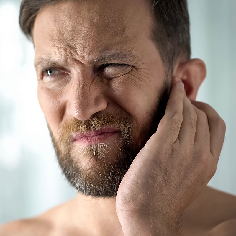Man holding ear in pain because he has an ear infection.